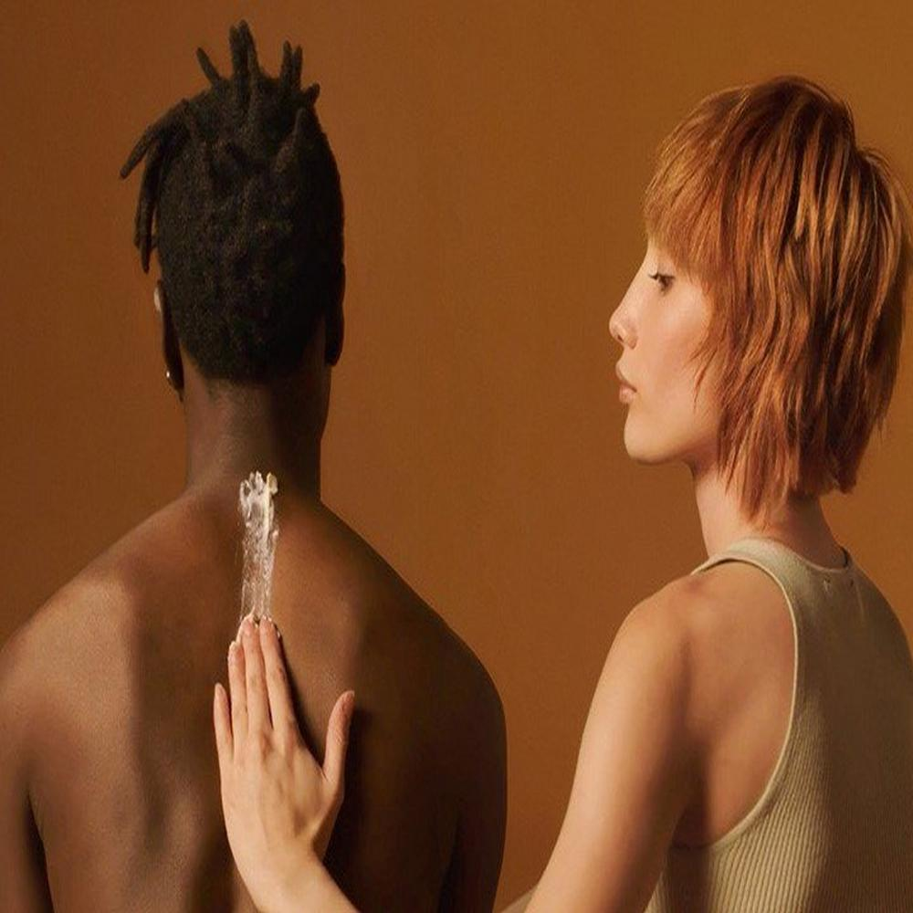 The Body Shop Woman spreading Body Butter onto man's back